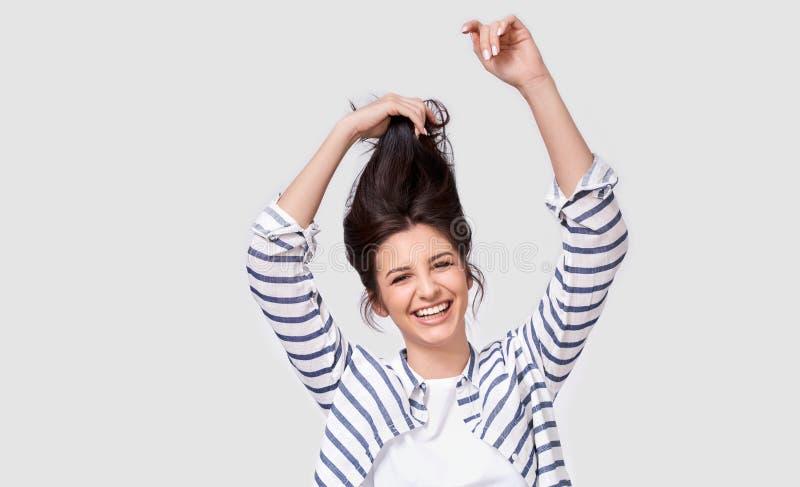 Studiobild der netten brunette Frau, die mit dem Haar lächelt und lacht, werfend über weißem Hintergrund spielt auf lizenzfreie stockfotografie