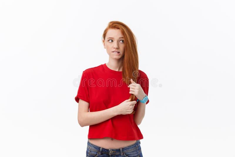Studiobild der netten Frau spielend mit dem Haar, das, werfend über weißem Hintergrund lächelt und lacht auf stockfoto