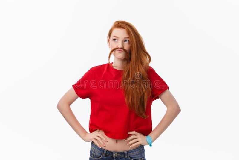 Studiobild der netten Frau spielend mit dem Haar, das, werfend über weißem Hintergrund lächelt und lacht auf stockfotos