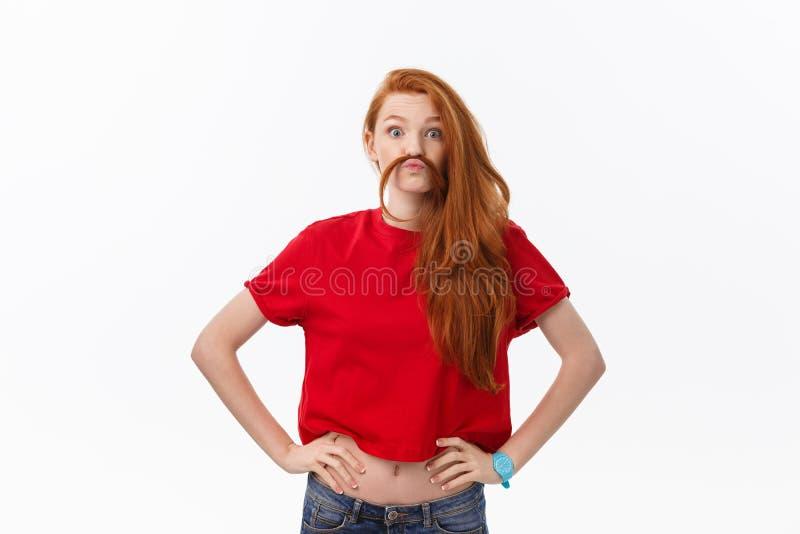 Studiobild der netten Frau spielend mit dem Haar, das, werfend über weißem Hintergrund lächelt und lacht auf lizenzfreies stockbild