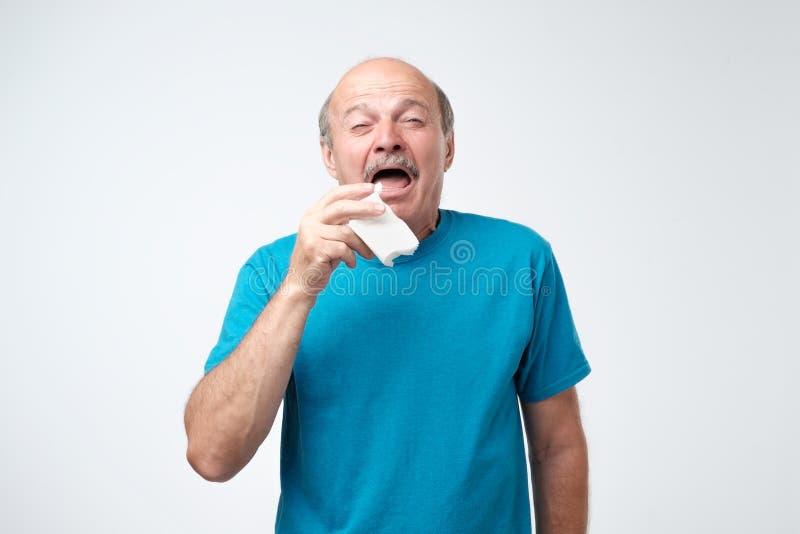 Studiobild des älteren Mannes mit Taschentuch Der kranke lokalisierte Kerl hat laufende Nase stockfoto