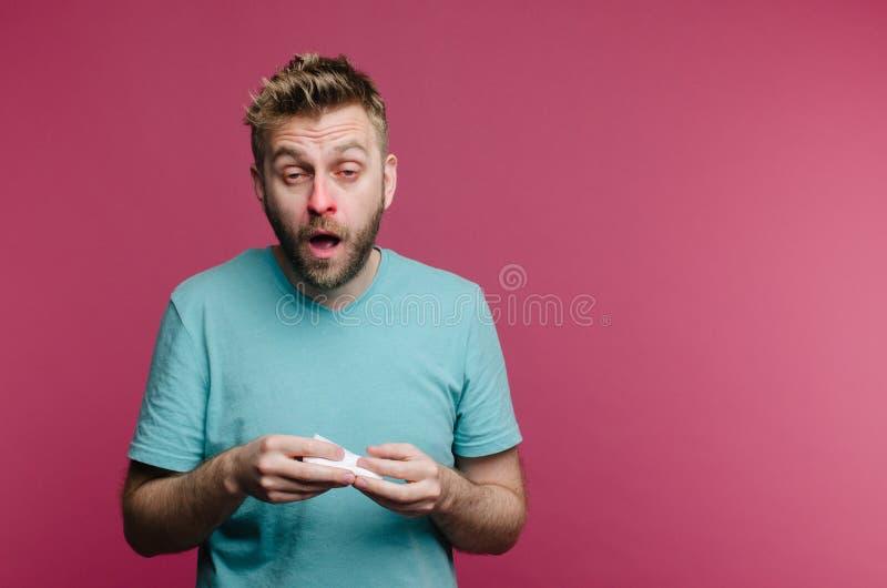 Studiobild från en ung man med näsduken som går att nysa Den isolerade sjuka grabben har den rinnande n?san mannen gör en bot för royaltyfri foto