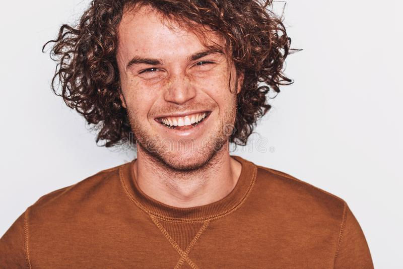 Studiocloseupen kantjusterade ståenden av den stiliga positiva mannen med sunt toothy leende som poserar för annonsering arkivbilder