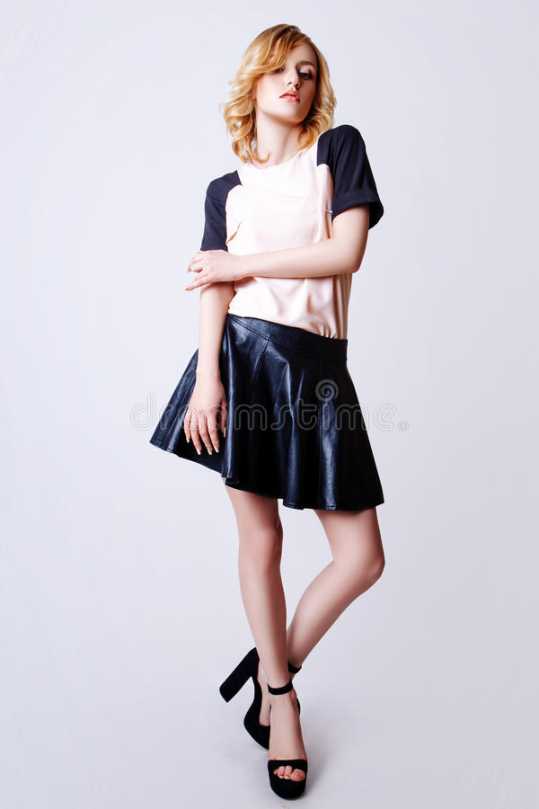 Studiofoto av den unga lockiga blonda kvinnan på vit bakgrund royaltyfri fotografi