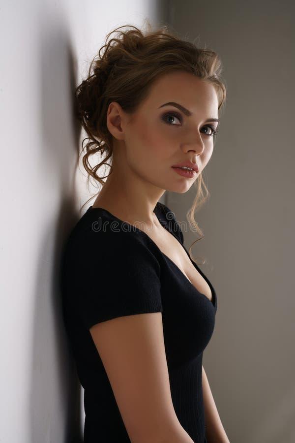 Studiofoto des netten jungen Brunette im schwarzen Kleid stockfotos