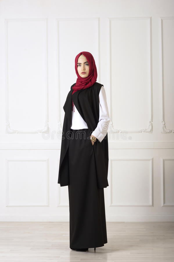 Studiofoto einer orientalischen Frau in einer modernen moslemischen Kleidung, in einem Schal und in einem Golduhrzeigerbrunnen lizenzfreie stockfotografie