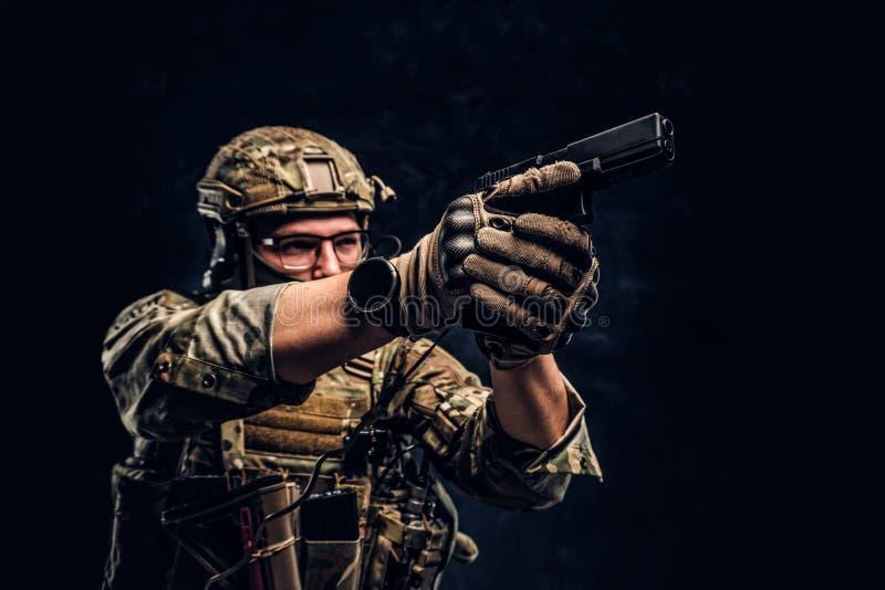 Studiofoto tegen een donkere geweven muur De eliteeenheid, speciale krachtenmilitair in camouflage eenvormige holding een pistool royalty-vrije stock foto's