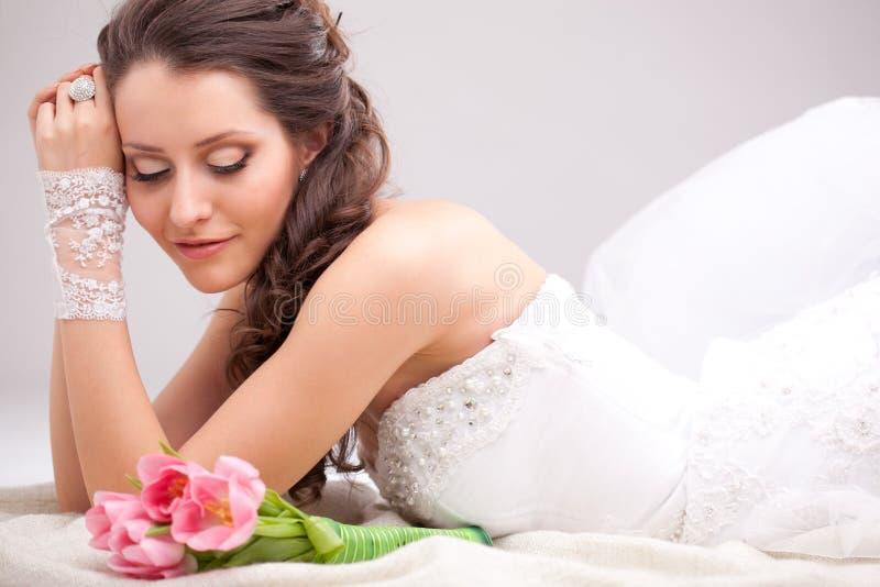 Studiofoto van een bruid die op de vloer liggen stock afbeelding