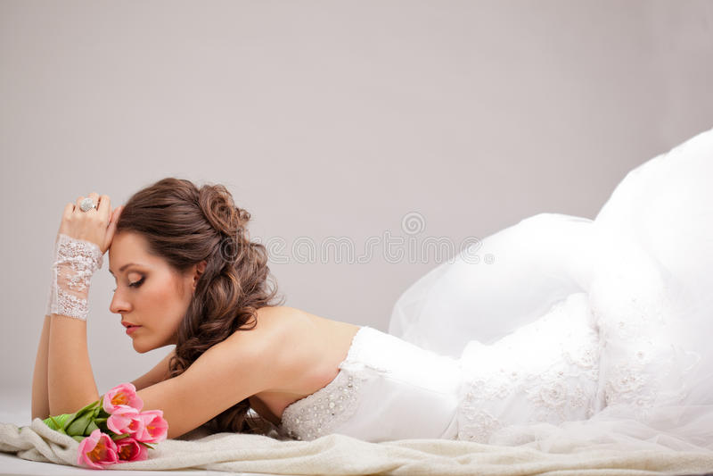 Studiofoto van een bruid die op de vloer liggen stock fotografie