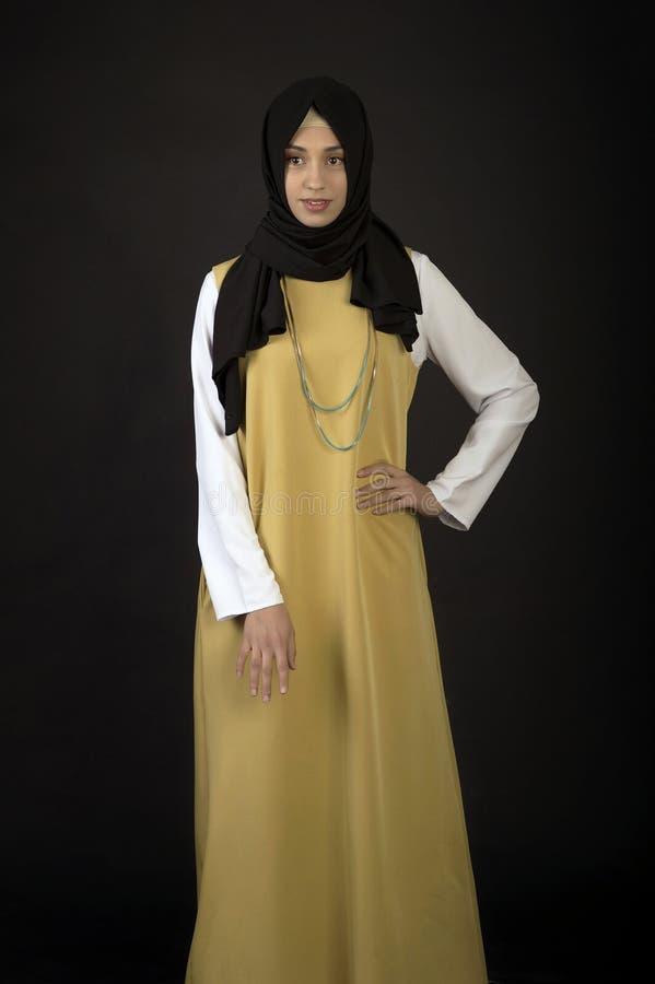 Studiofoto van een mooi jong vrouwen oostelijk type van gemiddelde lengte, op een donkere achtergrond, gekleed in de Moslimstijl royalty-vrije stock foto