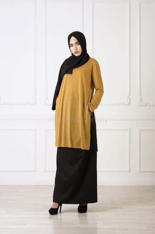 Studiofoto van een mooi jong vrouwen oostelijk type van gemiddelde lengte, op een lichte achtergrond, gekleed in de Moslimstijl royalty-vrije stock foto