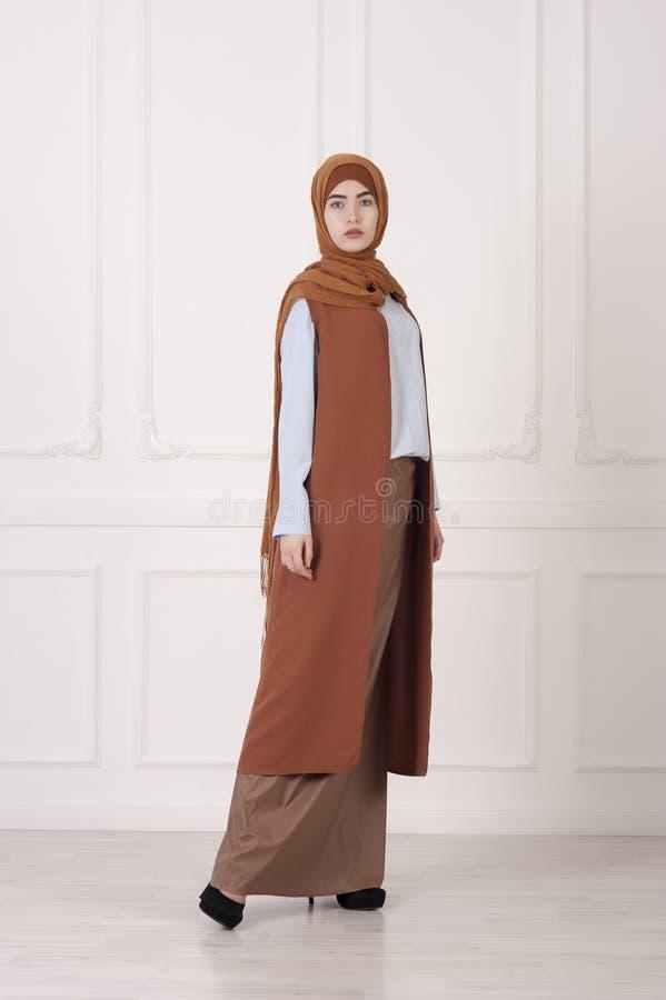 Studiofoto van een mooi jong vrouwen oostelijk type van gemiddelde lengte, op een lichte achtergrond, gekleed in de Moslimstijl stock afbeelding