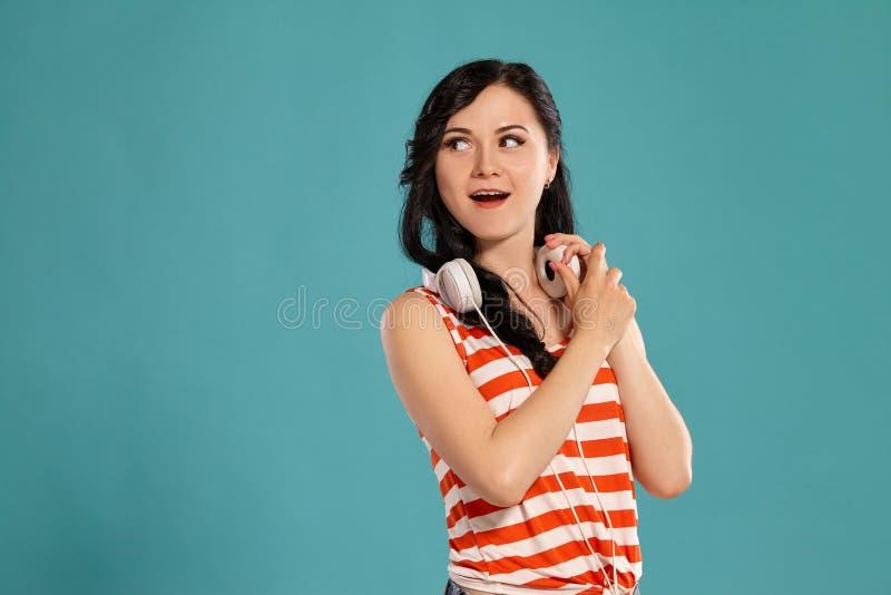 Studiofoto van het schitterende meisjestiener stellen over een blauwe achtergrond stock fotografie