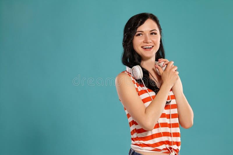 Studiofoto van het schitterende meisjestiener stellen over een blauwe achtergrond stock afbeelding
