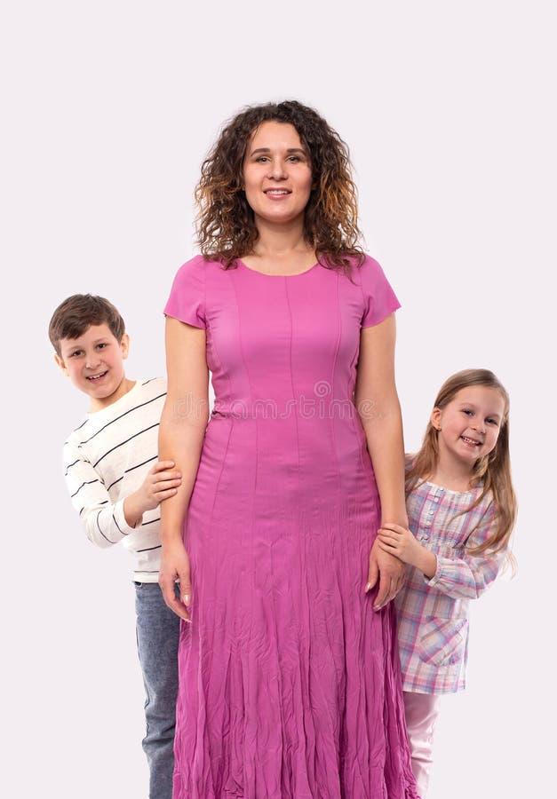 Studiofoto van mamma en haar twee kinderen, die pret hebben die uit van achter haar gluren, geïsoleerd royalty-vrije stock afbeeldingen
