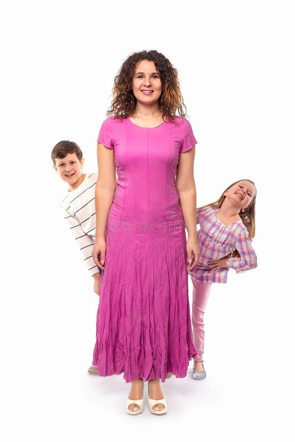 Studiofoto van mamma en haar twee kinderen, die pret hebben die uit van achter haar gluren, geïsoleerd stock afbeelding