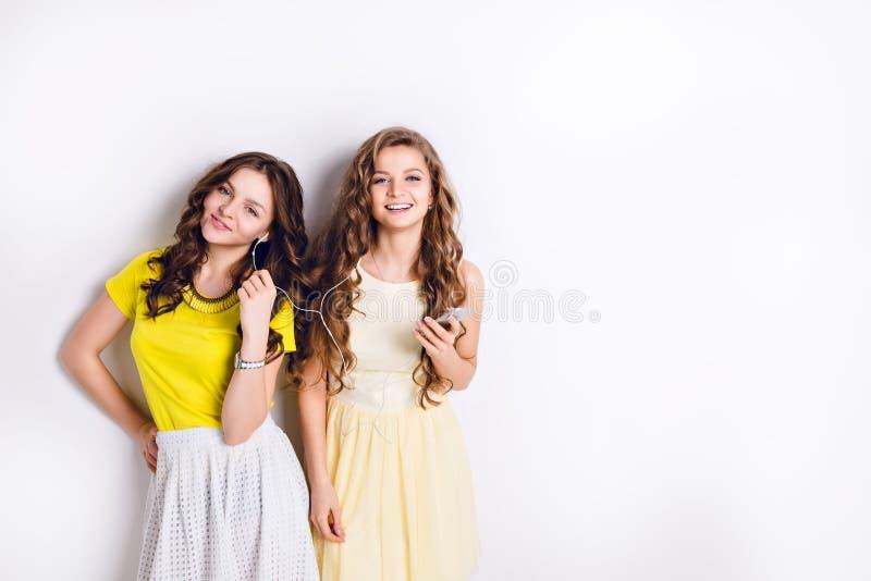 Studiofoto van twee bevindende glimlachende meisjes die aan muziek op een smartphone luisteren en pret hebben Het brunette draagt royalty-vrije stock fotografie