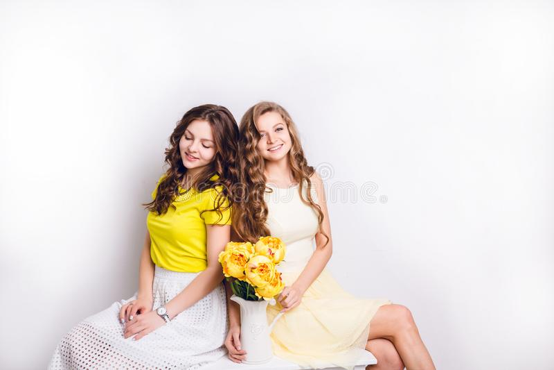 Studiofoto van twee glimlachende meisjes die schouder aan schouder zitten Het brunette draagt witte rok en gele T-shirt, en blond royalty-vrije stock afbeeldingen