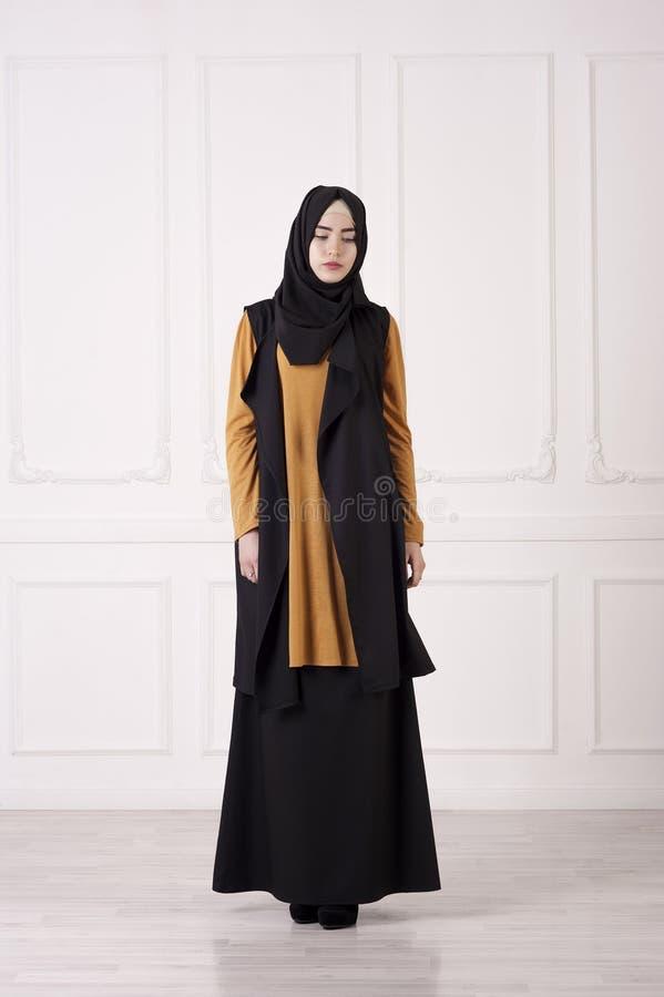Studiofotoet av en Caucasian för ung kvinna ser i de moderna muslimska kläderen, en halsduk på huvudet, höga häl, på en ljus clas royaltyfria bilder