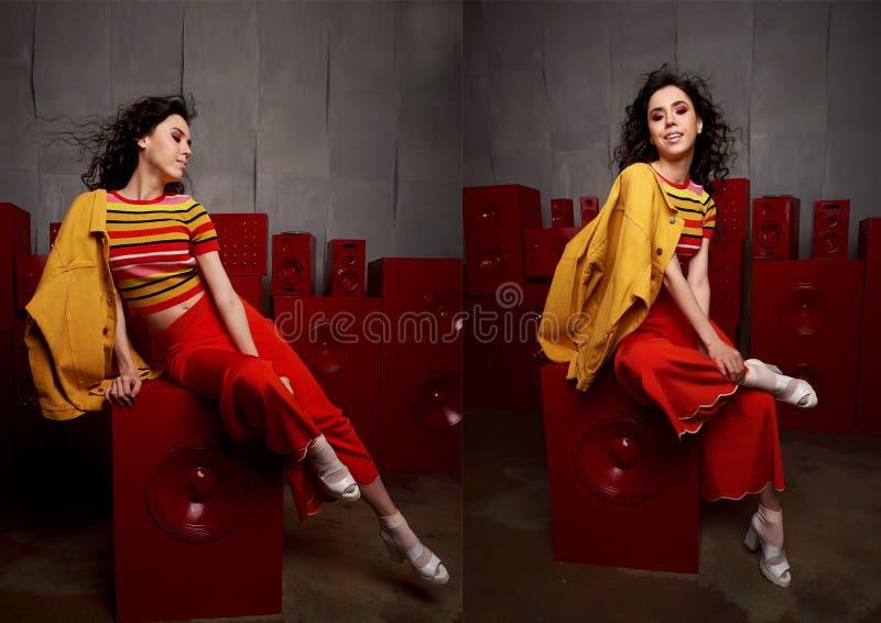 Studiomanier het schieten Het meisje in een heldere uitrusting, een bovenkant en broek flakkerde in rode en oranje tonen Brunette stock foto's