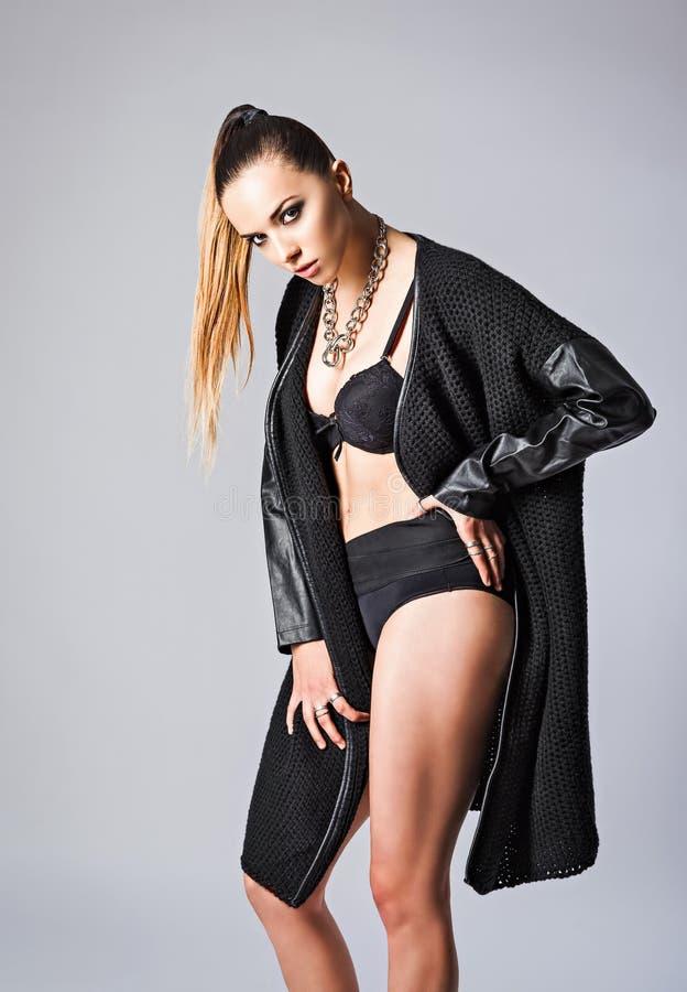 Studiomode geschossen: kühles sexy Mädchen, das schwarze Strickjacke trägt lizenzfreies stockbild