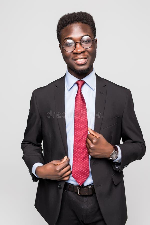 Studiomodestående av en stilig ung afrikansk amerikanaffärsman som bär en svart dräkt och band Isolerat på grå bakgrund royaltyfri foto