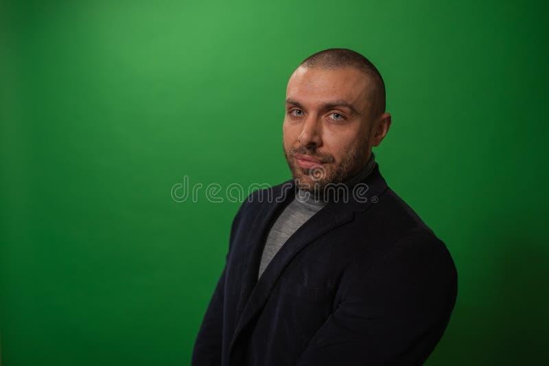 Studiomodestående i monokrom Elegant ung stilig allvarlig maniinstudio med grön bakgrund arkivbild