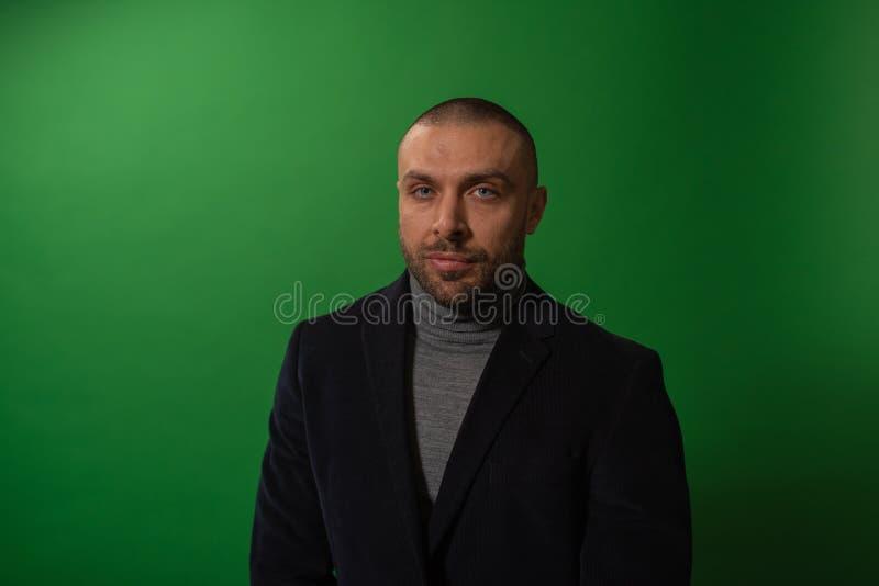 Studiomodestående i monokrom Elegant ung stilig allvarlig maniinstudio med grön bakgrund fotografering för bildbyråer