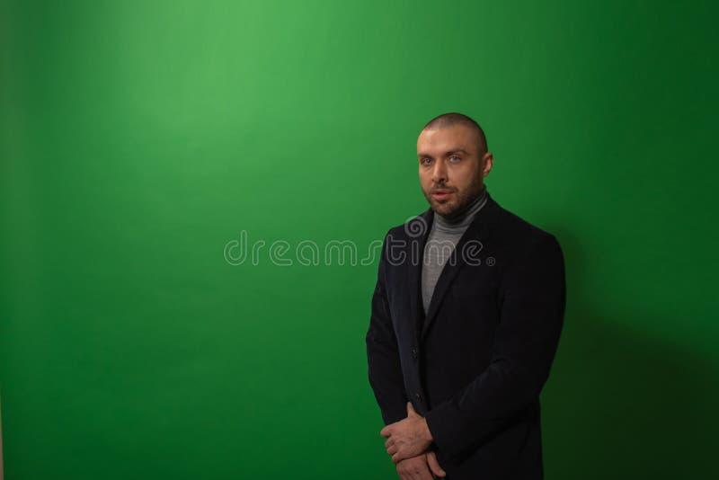 Studiomodestående i monokrom Elegant ung stilig allvarlig maniinstudio med grön bakgrund royaltyfri bild