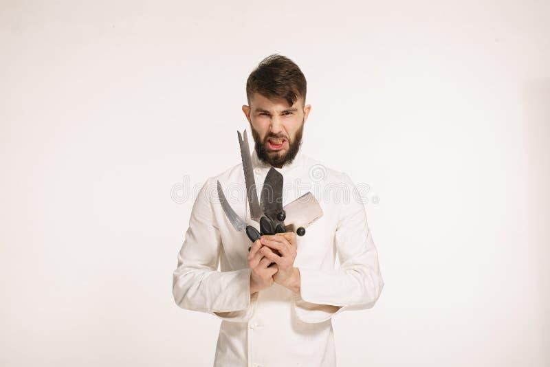 Studion sköt av en lycklig skäggig ung kock som rymmer skarpa knivar över vit bakgrund Kock med kniven Stilig ilsken allvarlig ch royaltyfri fotografi