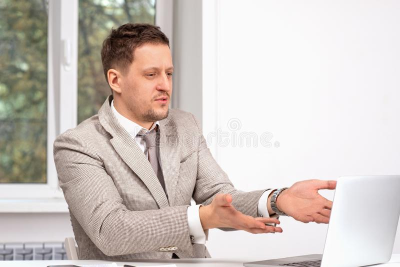 Studion sköt av en man som bär ett beige omslag, och ett band som arbetar på en bärbar dator med något, misshog eller indignerat  arkivbild