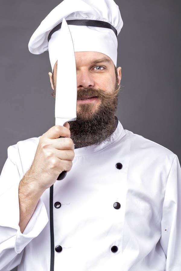 Studion sköt av en skäggig kock som rymmer en stor skarp kniv arkivfoton