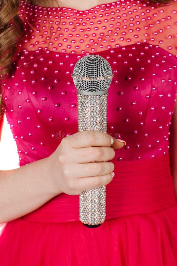 Studion sköt den härliga unga sjungande flickan i elegant röd klänninglo arkivfoto