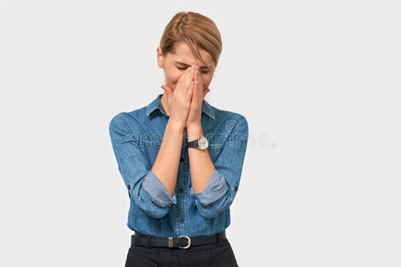 Studion som horisontalståenden av den upprivna affärskvinnan rynkar pannan, ska gråta, och att täcka med gömma i handflatan frams royaltyfria foton