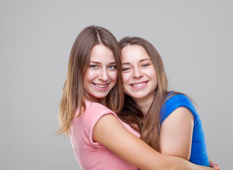 Studioportait av barn kopplar samman att omfamna för systrar fotografering för bildbyråer