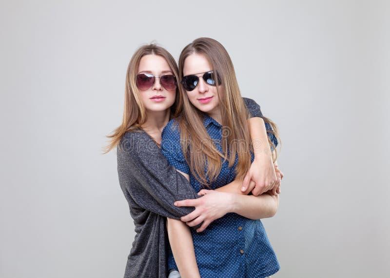 Studioportait av barn kopplar samman att omfamna för systrar arkivfoto