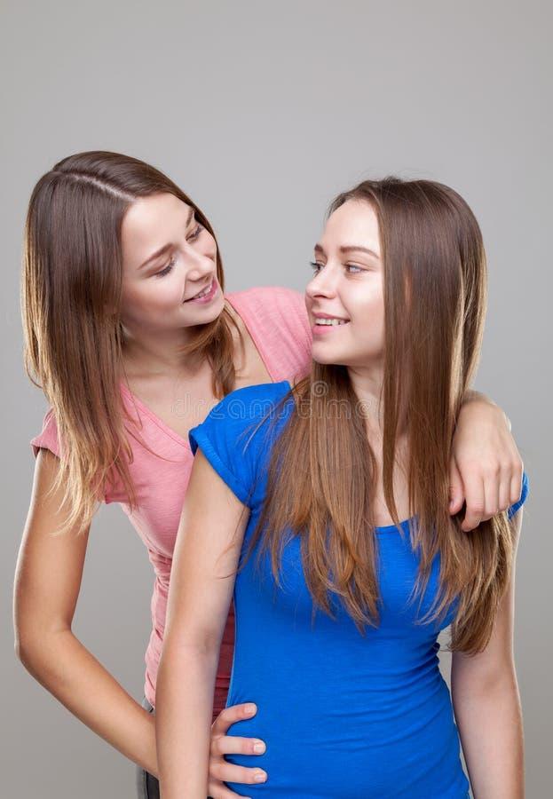 Studioportait av barn kopplar samman att omfamna för systrar royaltyfri foto