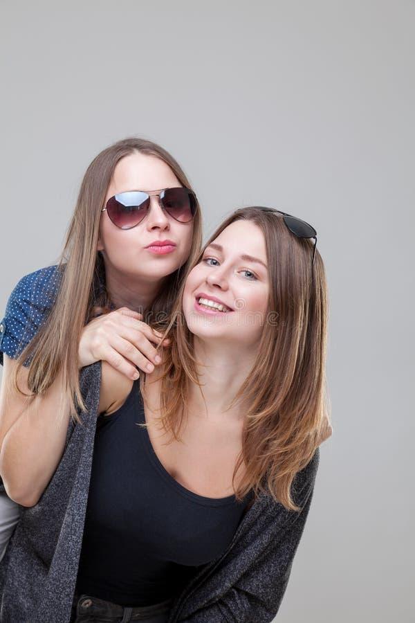 Studioportait av barn kopplar samman att omfamna för systrar arkivfoton