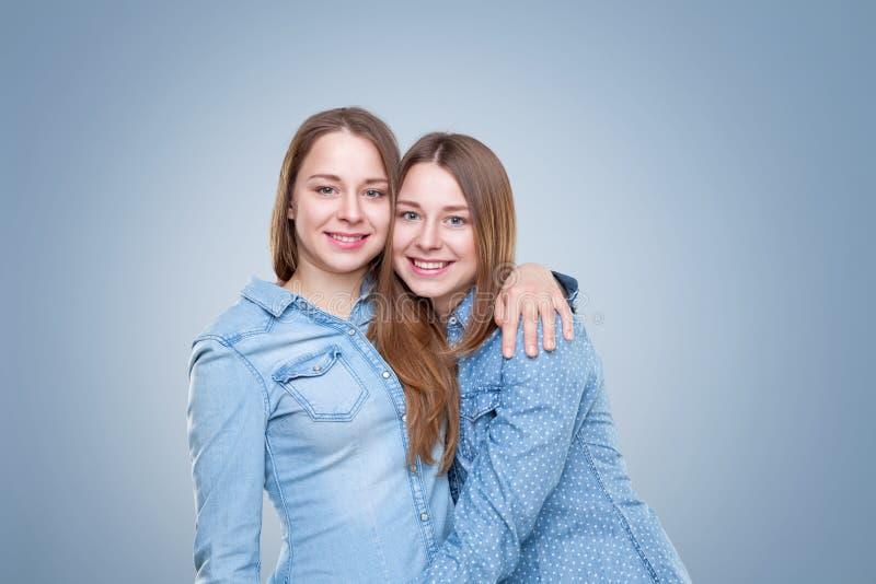 Studioportait av barn kopplar samman att omfamna för systrar arkivbilder
