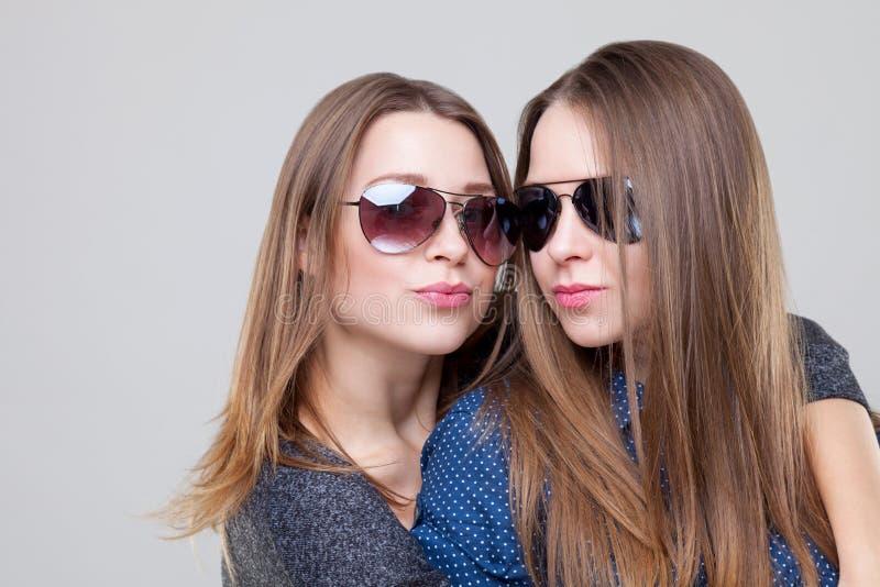 Studioportait av barn kopplar samman att omfamna för systrar royaltyfri fotografi
