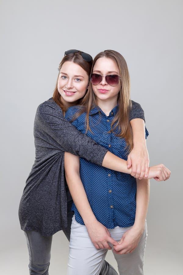 Studioportait av barn kopplar samman att omfamna för systrar arkivbild