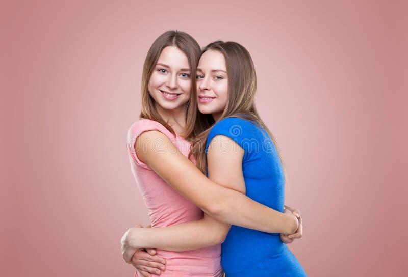 Studioportait av barn kopplar samman att omfamna för systrar royaltyfria bilder