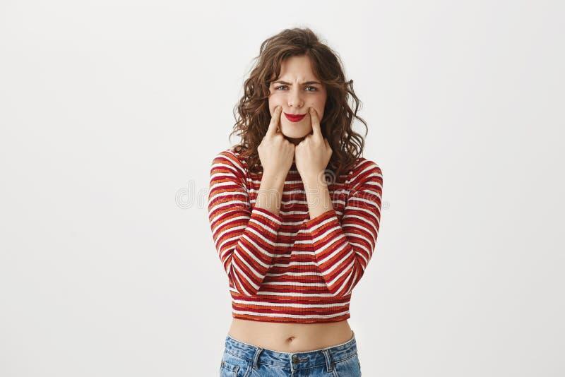 Studioporträt der goomy enttäuschten kaukasischen Frau im bauchfreien Oberteil Mund in Zwangslächeln mit den Zeigefingern ausdehn stockbilder