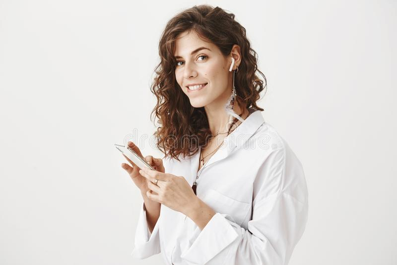 Studioporträt der heißen überzeugten Geschäftsfrau, die Smartphone und hörende Musik im drahtlosen Kopfhörer, beißende Lippe hält lizenzfreie stockbilder