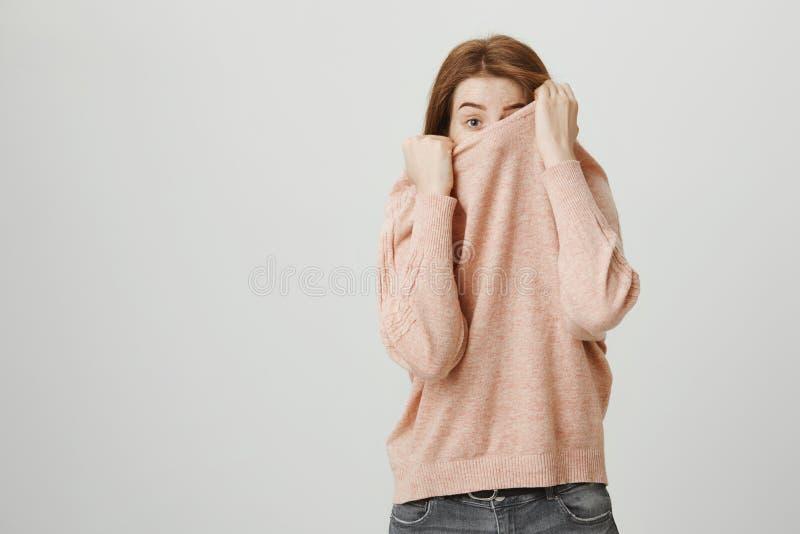 Studioporträt der lustigen europäischen Rothaarigefrau, die in ihrem Pullover beim Spähen mit einem Auge und anhebender Augenbrau lizenzfreie stockbilder