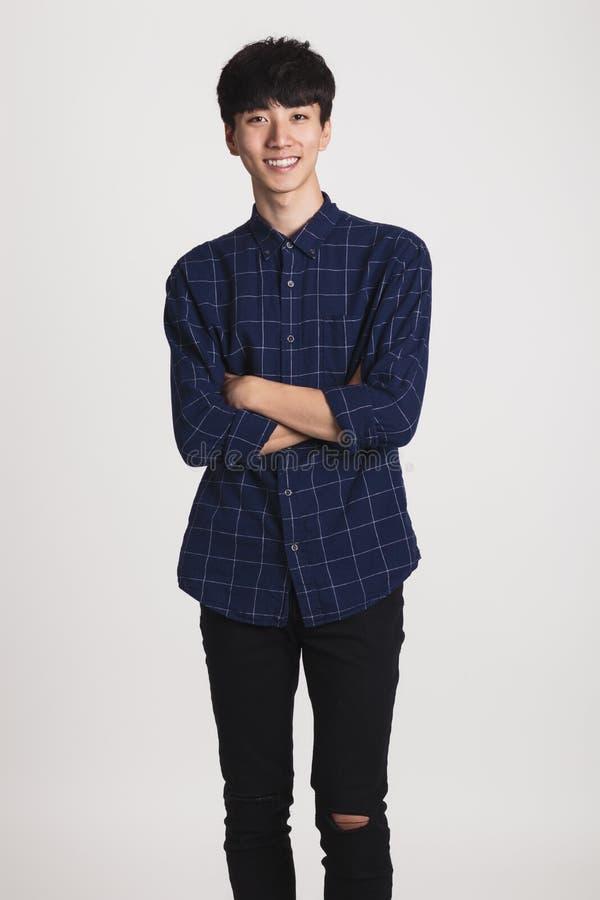Studioporträt des asiatischen jungen Mannes mit glücklichem Lächeln und dem Betrachten der Kamera lizenzfreie stockbilder