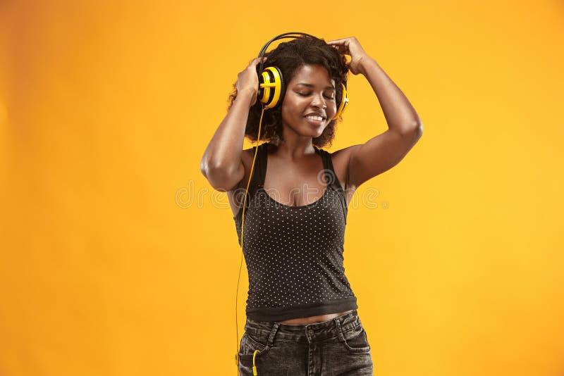 Studioporträt des glücklichen Lächelns des entzückenden gelockten Mädchens während des photoshoot Erstaunliche afrikanische Frau  stockbilder
