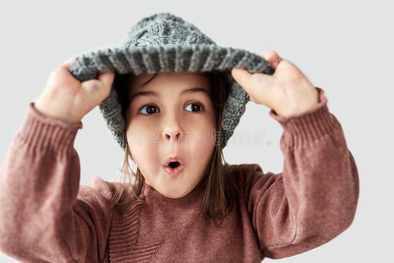 Studioporträt des kaukasischen kleinen Mädchens im warmen grauen Hut des Winters, hat das Gesicht und tragende Strickjacke überra stockfoto