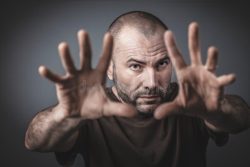 Studioportr?t des kaukasischen Mannes mit den offenen H?nden und den Armen vorw?rts ausgestreckt lizenzfreie stockfotos