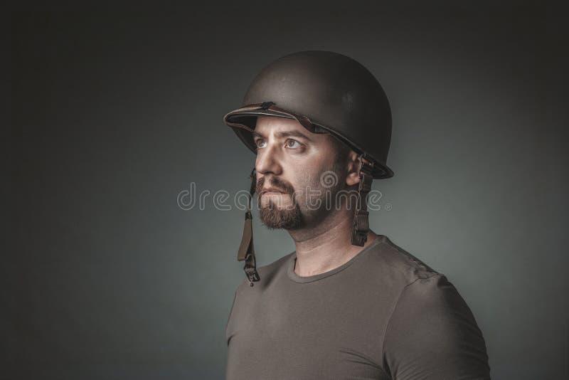 Studioporträt des Mannes mit dem Militärsturzhelm, der weg schaut stockfotografie
